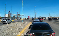 Baja - Mexicali - USA Border - Calexico II - Cars in left lane waiting to enter border complex, and others making left turns from the middle lane